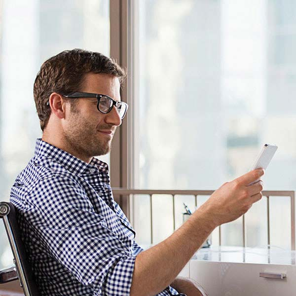 Man reading a mobile device near an indoor window.