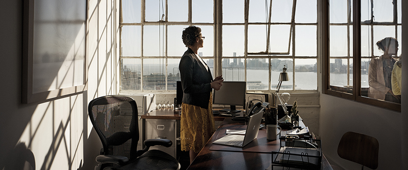 Woman standing in office gazing out window