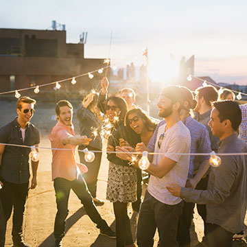Grupo de personas felices rodeadas de guirnaldas con luces celebran algo con luces de bengala.