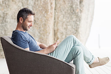 Image of man on a balcony, looking at his smartphone