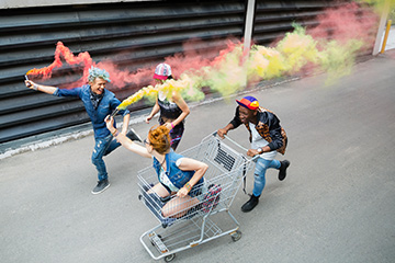 Young people with smoke flares and a shopping cart