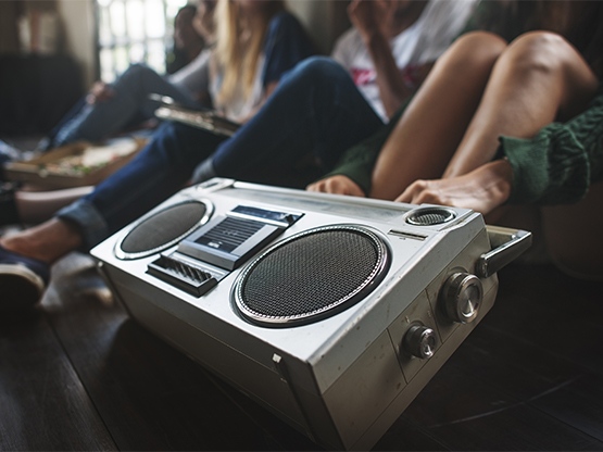 Portable stereo being held in a group of young people.