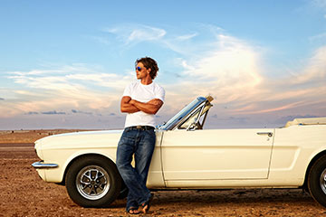 Man wearing sunglasses leans against a vintage Ford Mustang beside a highway.