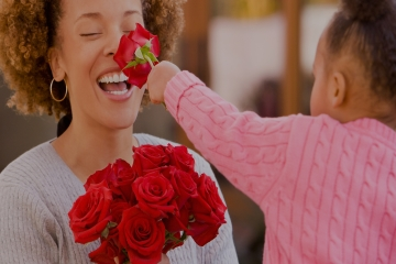 Woman laughs as a child presses a red rose to her nose.