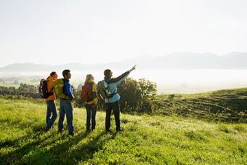 4 personas en una colina con hierba con ropa de senderismo disfrutando del paisaje