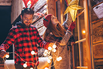 Young couple hanging holiday decorations on rustic building