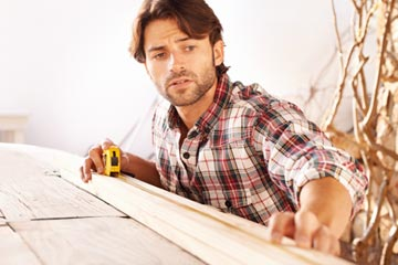 Man using measuring tape on wood.