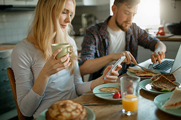 Man and woman eating breakfast and looking at cell phone.