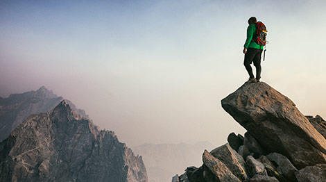 Man looking out at mountains from on top of a rock formation.