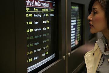 Woman viewing airport arrival information on monitor.