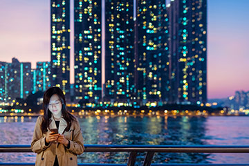 Woman viewing smartphone on modern city waterfron