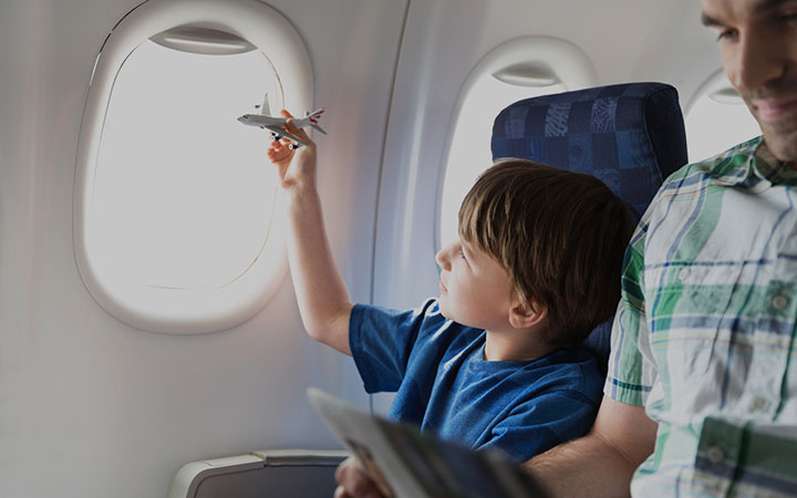 Boy playing with a toy airplane while on an airplane with his dad.