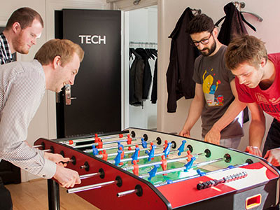Photo of momondo workers playing at a foosball table during a Bing Blasts workshop.