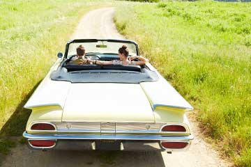 Man and woman driving on a dirt road in a vintage convertible.
