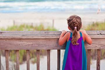 Small girl looks over railing toward a beach.