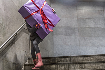 woman carrying large present down stairs