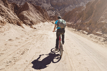 Man wearing backpack rides a mountain bike on a desert canyon road.