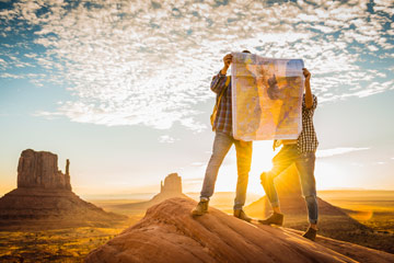 Photo of man and woman standing on a rock in the desert and looking at a map