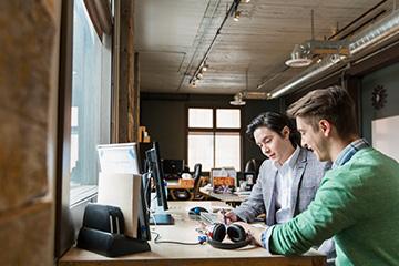 Teammates collaborating at a computer