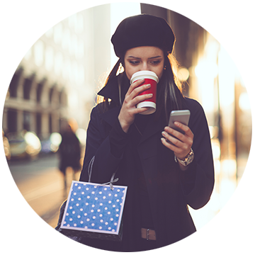 Woman sipping coffee while checking smartphone