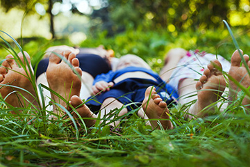 Children laying in grass with feet pointing up