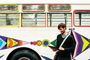 Ein Mann steht auf einem Bus und schaut auf Ihren Computer