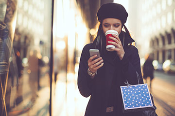 Woman drinking coffee and checking smartphone